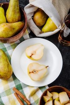 Vista laterale di metà pera su un piatto bianco e un bicchiere di limonata su una tovaglia a quadri