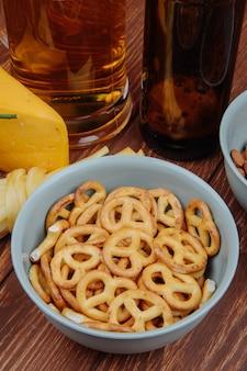 Vista laterale di mini ciambelline salate in una ciotola e formaggio con birra su rustico