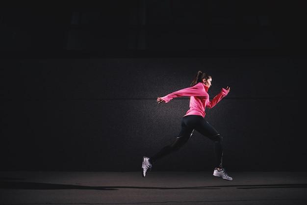 Vista laterale di movimento della ragazza corrente dell'atleta sexy di misura in abiti sportivi alla via davanti alla parete grigia.
