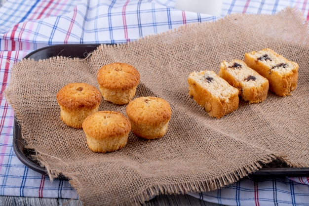 Vista laterale di muffin e pan di spagna su tela di sacco