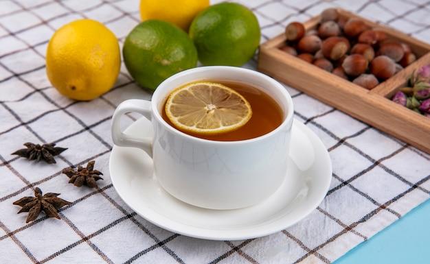 Vista laterale di nocciole con noci e una tazza di tè al limone su un asciugamano a scacchi