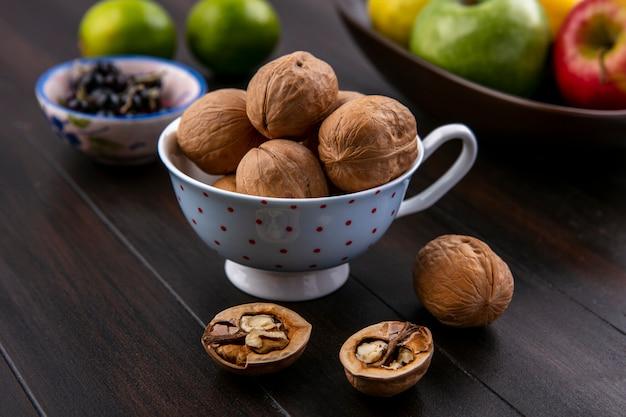 Vista laterale di noci in una tazza con mele lime e ribes nero su una superficie di legno