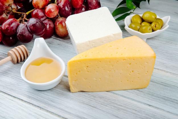 Vista laterale di pezzi di formaggio con miele, uva fresca e olive in salamoia sul tavolo di legno grigio