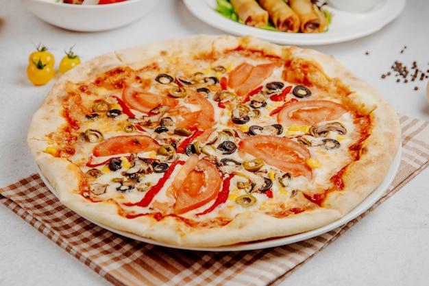 Vista laterale di pizza con pomodori funghi e olive