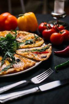 Vista laterale di pizza italiana affettata con i peperoni variopinti funghi rucola e formaggio delle olive nere su un piatto di legno