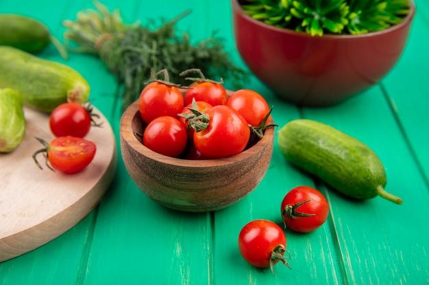 Vista laterale di pomodori in una ciotola e aneto di cetriolo intorno sul verde
