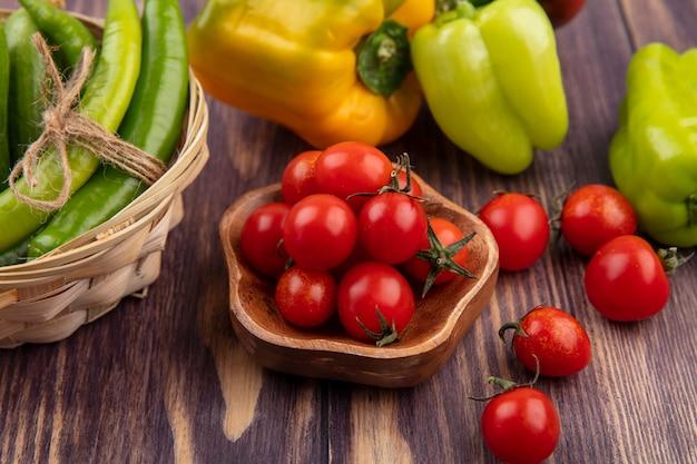 Vista laterale di pomodori in una ciotola e peperoni nel carrello e su legno