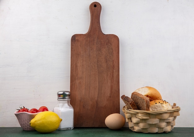 Vista laterale di pomodori su una ciotola con agitatore a stecche di limone un bcuket di pane su bianco