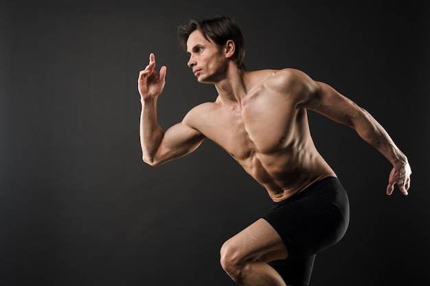 Vista laterale di posa muscolosa senza camicia dell'uomo