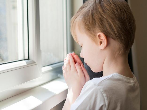 Vista laterale di pregare del ragazzino