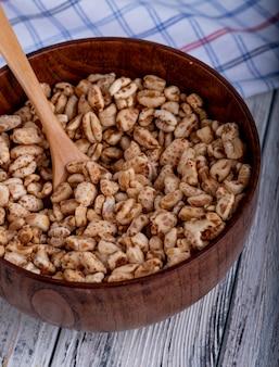 Vista laterale di riso dolce soffiato in caramello in una ciotola di legno