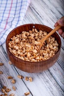 Vista laterale di riso dolce soffiato in una ciotola di legno con un cucchiaio rustico