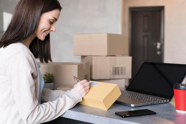 Vista laterale di scrittura della donna sulla scatola sul lavoro