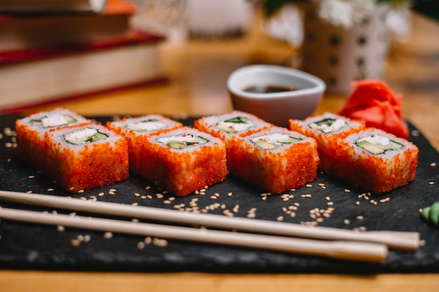 Vista laterale di set di sushi rotoli con crema di granchio crema di formaggio e avocado nel caviale di pesce volante con salsa di soia su una lavagna nera