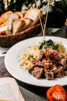 Vista laterale di spaghetti con pezzi di carne e pomodoro su una tavola di legno