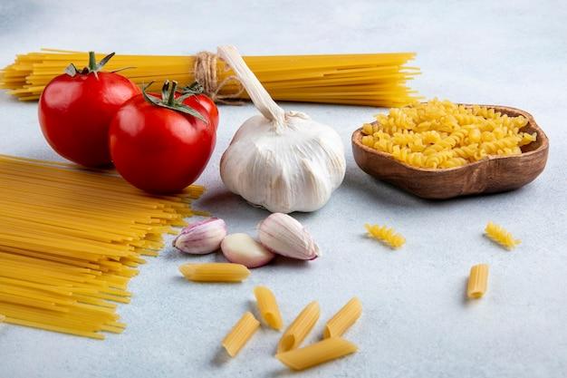 Vista laterale di spaghetti crudi con aglio e pomodori su una superficie grigia