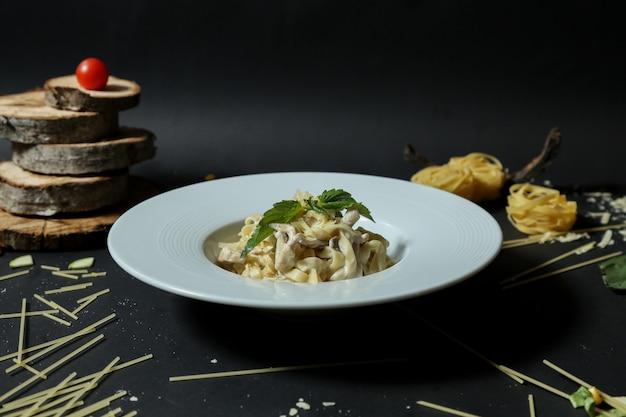 Vista laterale di sumakh dei funghi di pollo del formaggio cremoso di fettuccini della pasta