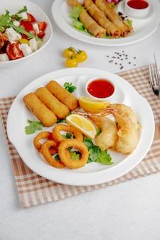 Vista laterale di tempura di calamari e gamberi e bastoncini di formaggio fritto su un piatto bianco
