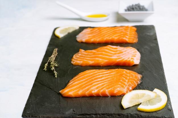Vista laterale di tre pezzi di salmone crudo su una tavola di ardesia e spicchi di limone con olio d'oliva e sale nero