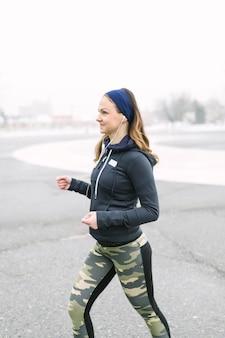 Vista laterale di un atleta femminile che si esercita in inverno