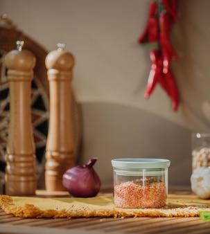 Vista laterale di un barattolo di vetro con le lenticchie rosse su una tavola di legno
