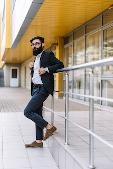 Vista laterale di un bel giovane uomo d'affari in piedi vicino alla ringhiera