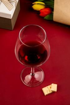 Vista laterale di un bicchiere di vino con cioccolata bianca e un mazzo di tulipani di colore rosso e giallo sul tavolo rosso
