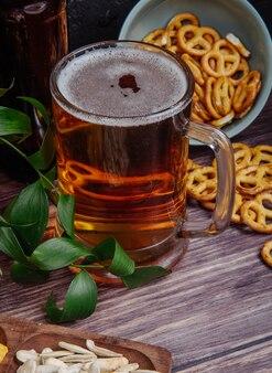 Vista laterale di un boccale di birra con mini salatini su rustico