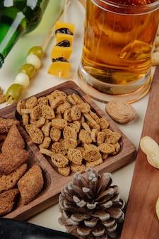 Vista laterale di un boccale di birra con snack salati pane cracker noci e olive in salamoia