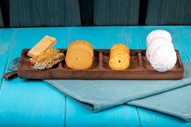 Vista laterale di un bordo di legno con i kozinaki dolci dei biscotti delle caramelle gommosa e molle zephyr bianche e bianche sul blu