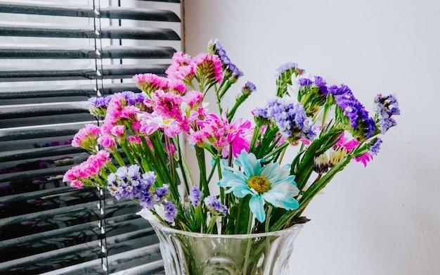 Vista laterale di un bouquet di rosa bianco viola e blu colore statice e fiori di crisantemo in un vaso di vetro a sfondo bianco muro