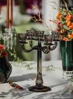 Vista laterale di un candeliere di vetro su una tavola di legno bianca