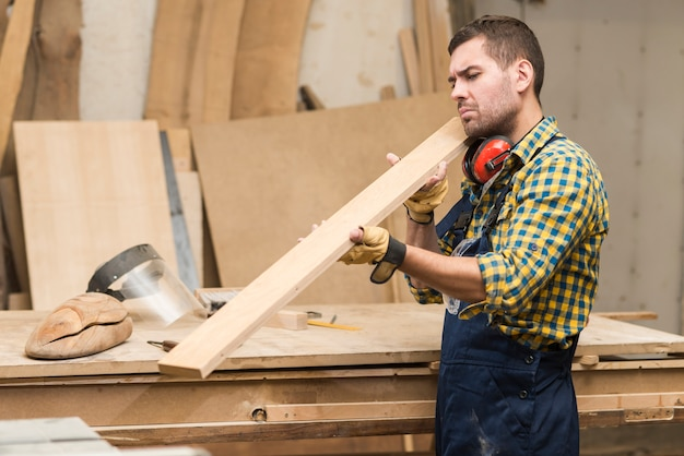 Vista laterale di un carpentiere maschio che esamina la plancia di legno
