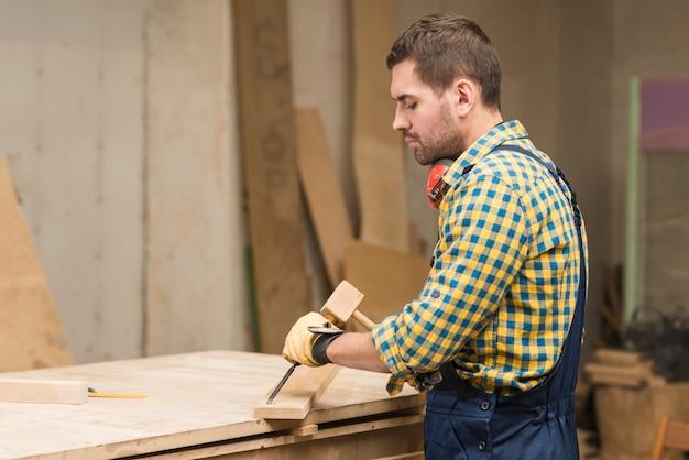 Vista laterale di un carpentiere maschio che intaglia sul legno con lo scalpello nell'officina