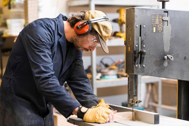 Vista laterale di un carpentiere maschio che prende misura sul banco da lavoro