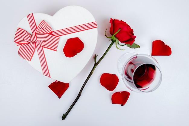 Vista laterale di un contenitore di regalo a forma di cuore e un bicchiere di vino con la rosa di colore rosso e petali su fondo bianco