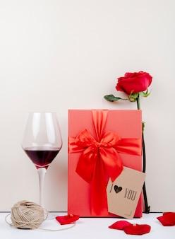 Vista laterale di un contenitore di regalo rosso con un arco e una rosa rossa con la piccola cartolina e un bicchiere di vino una palla di corda su fondo bianco