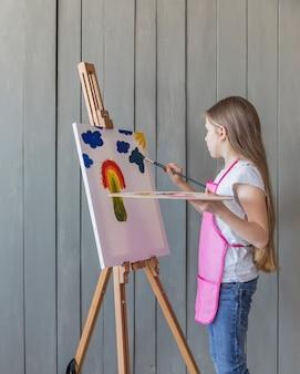 Vista laterale di un disegno della ragazza con il pennello sul cavalletto contro la plancia di legno