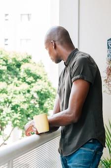Vista laterale di un giovane africano in piedi nel balcone tenendo in mano la tazza di caffè