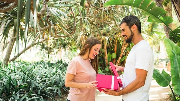 Vista laterale di un giovane che mostra il regalo alla sua ragazza