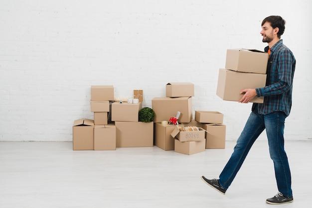 Vista laterale di un giovane che porta le scatole di cartone a disposizione che cammina nella sala