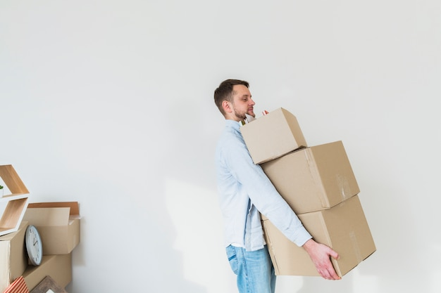 Vista laterale di un giovane che trasporta la pila di scatole di cartone contro il muro bianco