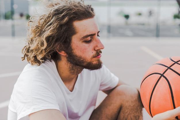 Vista laterale di un giovane con la pallacanestro