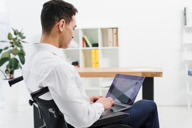 Vista laterale di un giovane disabile che si siede sulla sedia a rotelle che utilizza computer portatile nell'ufficio
