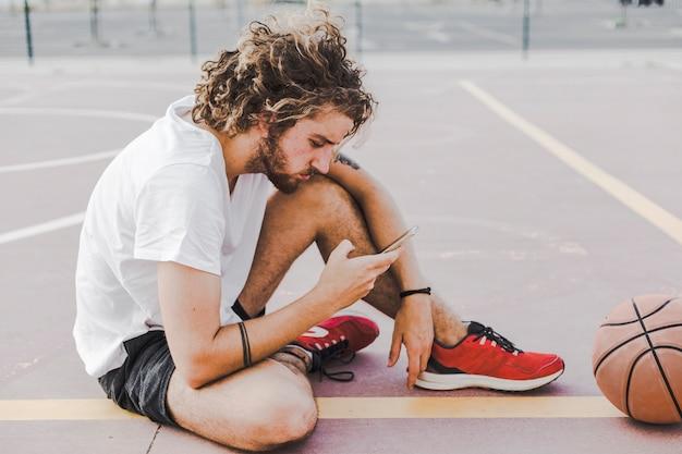 Vista laterale di un giovane giocatore di basket maschile utilizzando smartphone
