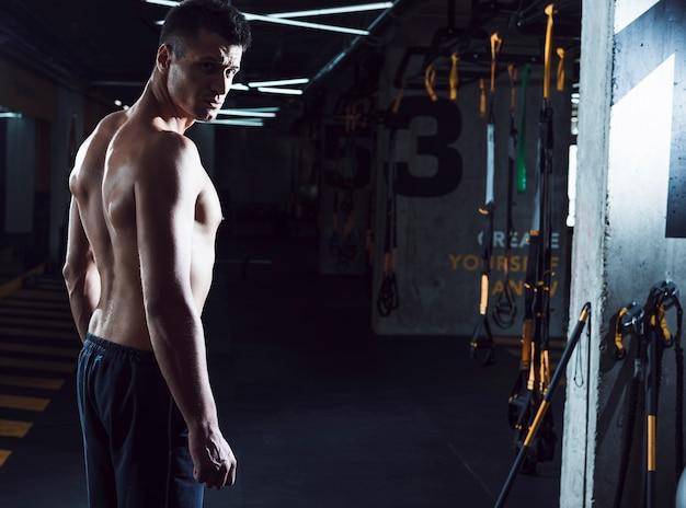 Vista laterale di un giovane muscolare in piedi in palestra