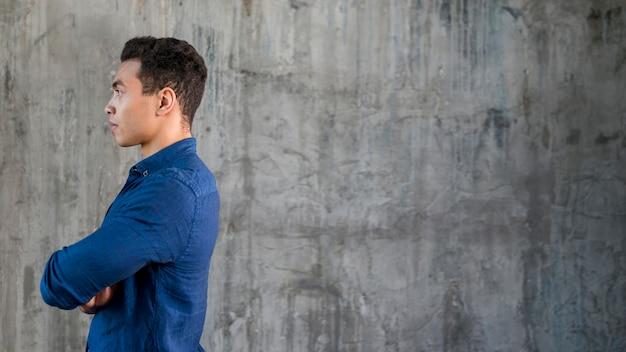 Vista laterale di un giovane serio in piedi su sfondo grigio concreto