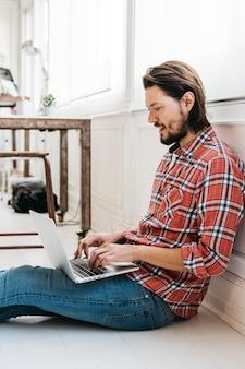 Vista laterale di un giovane sorridente che si siede sul pavimento di legno duro che digita sul computer portatile