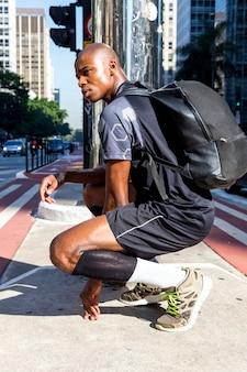 Vista laterale di un giovane sportivo uomo africano con il suo zaino accovacciato in mezzo alla strada