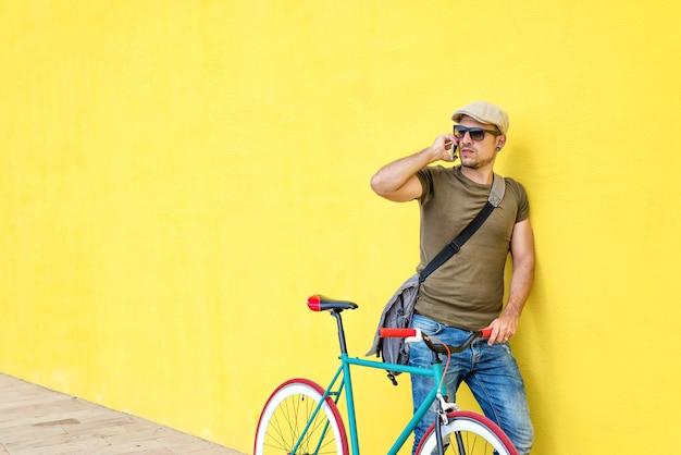 Vista laterale di un giovane uomo adulto con una bici d'epoca e indossando abiti casual